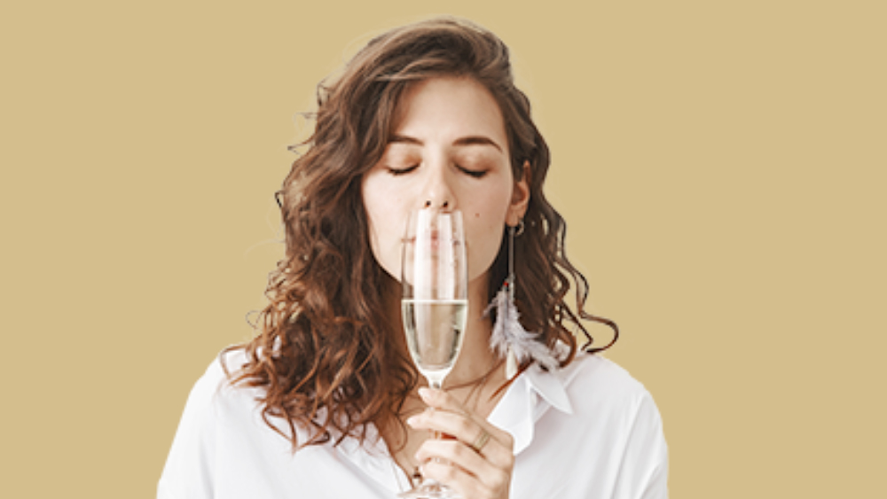 curly girl sniffing the taste of a glass of prosecco
